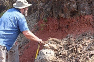 Paul Renne inspects a reddened soil horizon between lava flows, a so-called red bole. Mark Richards photo.