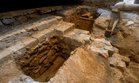 Archaeologists examine a thick foundation for an extension on the west side of the original kitchen structure. Researchers do not yet know for what the extension was used.