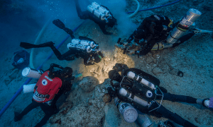 Archaeologists Brendan Foley, Theotokis Theodoulou and Alex Tourtas excavate the Antikythera Shipwreck skeletal remains, assisted by Nikolas Giannoulakis and Gemma Smith. Photo by Brett Seymour, EUA/WHOI/ARGO