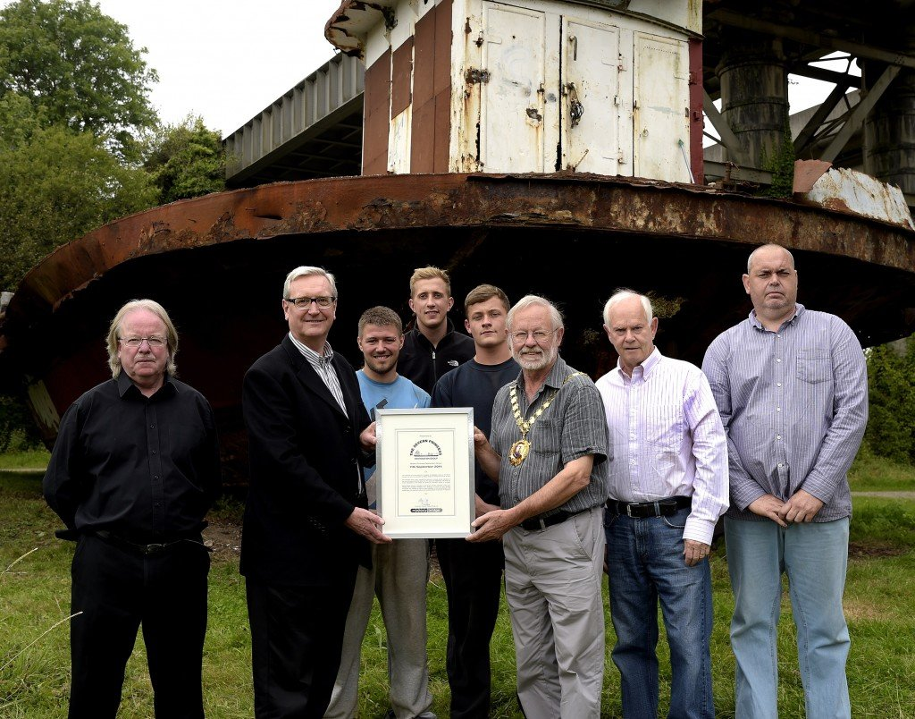 Philip Clegg, Production Director of Mabey Bridge presents the Mayor of Chepstow, Cllr Ned Heywood with a commemorative certificate on the completion of stabilisation work. Pictured left to right: Tim Ryan (Severn Princess Restoration Group), Philip Clegg (Mabey Bridge), Ashley Flounders, Joshua Jones and Joseph Covell (Mabey Bridge apprentices), Cllr Ned Heywood, Richard Jones (Severn Princess Restoration Group), Gary Bollen (Severn Princess Restoration Group volunteer)