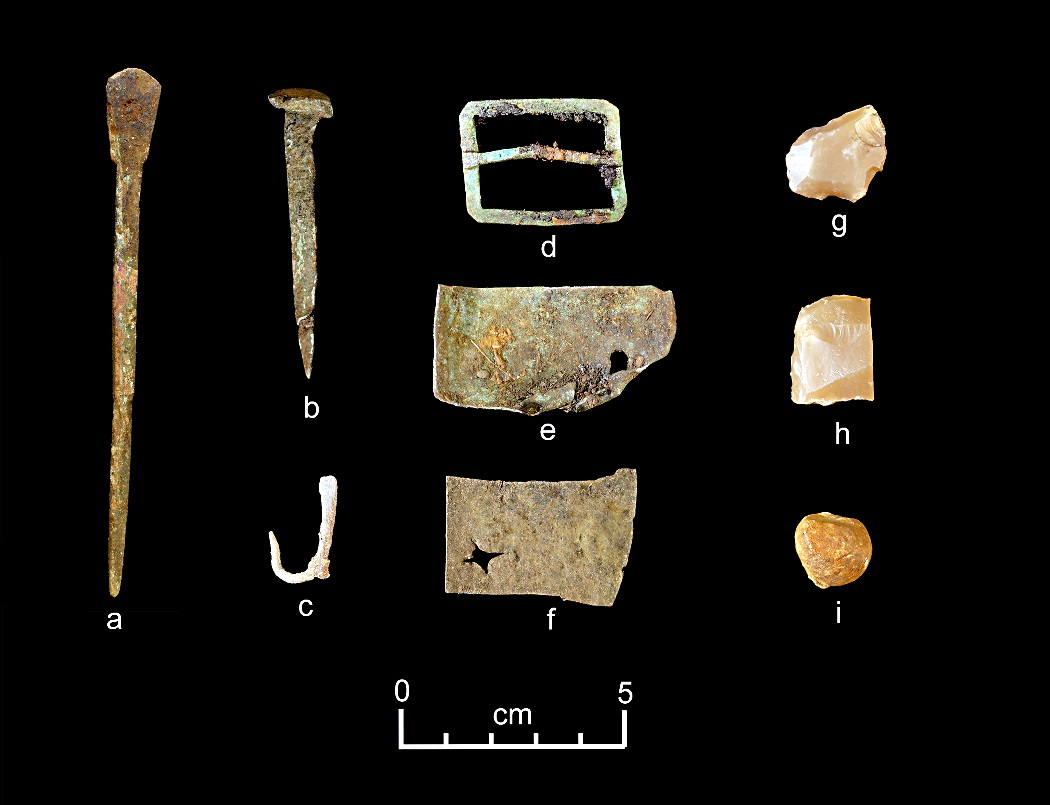 A representative collection of artifacts discovered in July 2015 includes (from left) part of a set of dividers, a nail, a fishhook, a buckle, sheet copper, gun flints and a musket ball. Credit: Dave McMahan, Sitka Historical Society